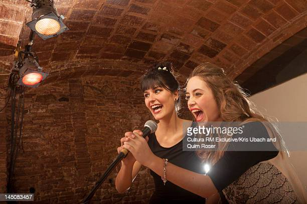 Women singing together in microphone