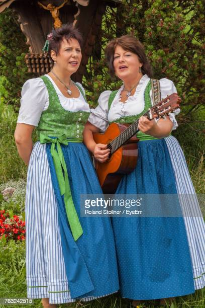 Women Singing While Standing On Grassy Field Against Tree