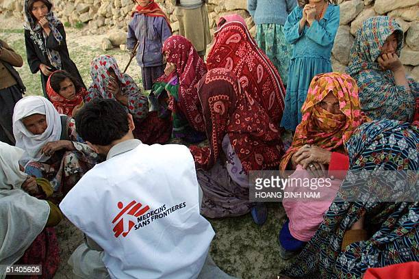 Women sit around an aid worker from Medecins Sans Frontieres waiting for their turn to receive medications at the mountainous village of Ashor hit by...