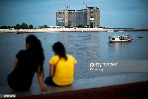 Women sit by the Tonle Sap river as a development by Sokha Hotels Resorts a unit of Sokimex Group stands under construction in Phnom Penh Cambodia on...