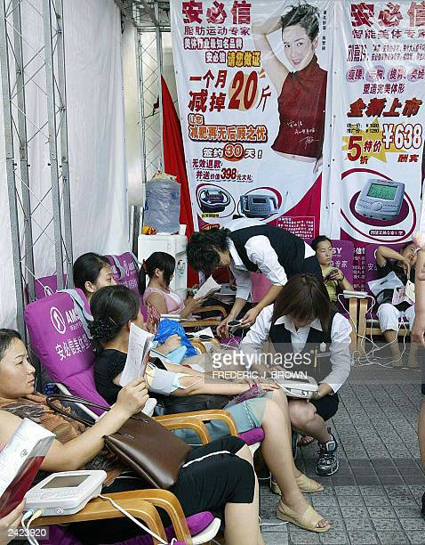 Women sit for a free health check 22 August 2003 in Beijing at a stall promoting its cosmetic and beauty products targetted toward women wanting to...