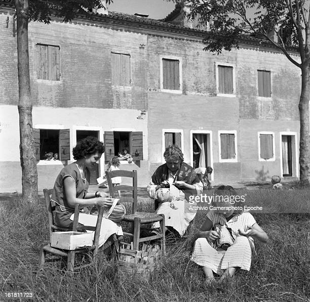Women sit in the garden making lace Burano Venice 1949