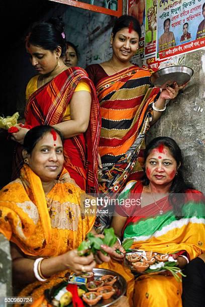 Women sit offering pooja to Bipadtarini Devi in Dhaka Bangladesh July 25 2015 During the ritual of people from Hindu community take long day ritual...