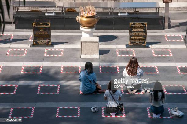 Women sit on a social distancing square while praying in front of a shrine near Ratchadamri Road. The Thai government has applied social distancing...