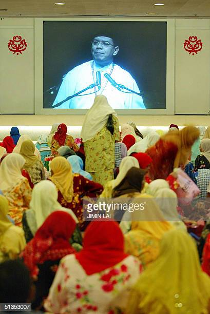 Women sit on the floor as they listen to a speaker on a projector screen at the ruling United Malays National Organisation general assembly in Kuala...