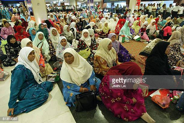 Women sit on the floor as they watch a projector screen showing a speaker at the ruling United Malays National Organisation general assembly in Kuala...