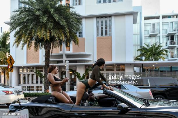 Women sit on top of a car seat as they drive thru Miami Beach Florida on June 26 2020 They are itching for a good time after months of lockdown and...