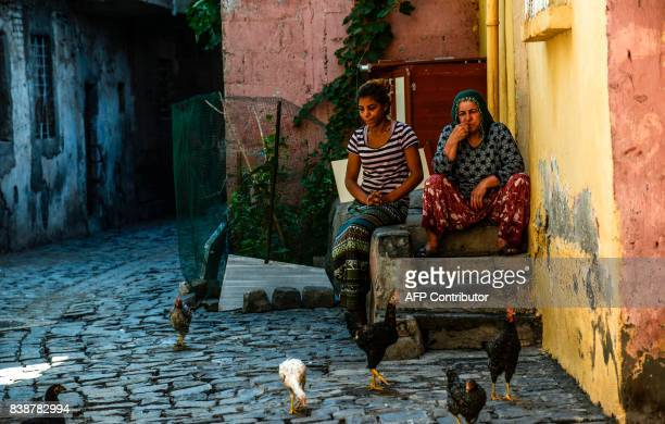 Women sit outside a house and look at hens and roosters during an urban rebuilding project in the Sur district in southeastern province of Diyarbakir...