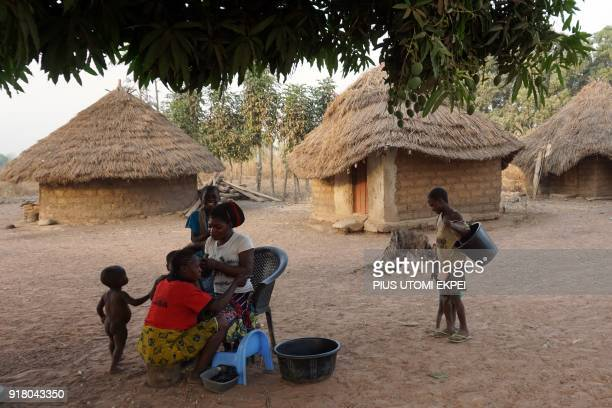 Women sit under a tree with children in Tse Chagu on the outskirts of Makurdi capital of Benue State in northcentral Nigeria on January 4 2018...