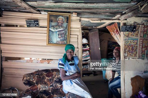 A women sits in her small tworoom house in with her Nelson Mandela framed portraits on the walls on May 7 2018 in Ndevana Eastern Cape Province South...