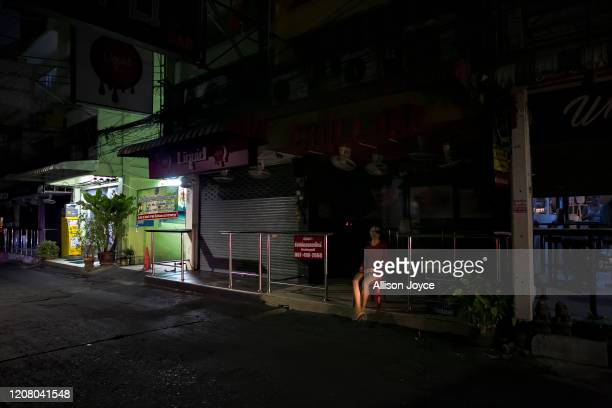 A women sits outside a bar on a normally busy bar and party street as it lies mostly empty on March 23 2020 in Pattaya Thailand On March 18th Pattaya...