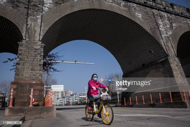 A women sits wearing a protective mask rides a bike through the old city gate on February 9 2020 in Wuhan China Flights trains and public transport...
