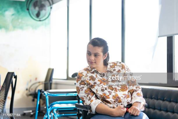 women sitting at conference room table. walking aid next to her. - thisisaustralia stock pictures, royalty-free photos & images