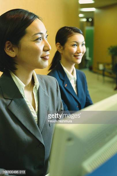 Women sitting at reception desk, smiling