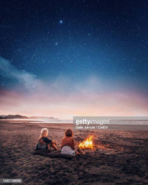 women sitting by bonfire at beach against sky - bonfire stock photos and pictures