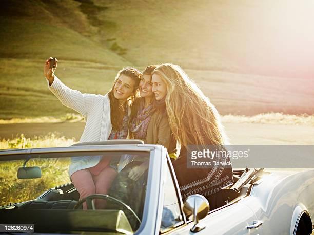 Women sitting in backseat taking digital photo