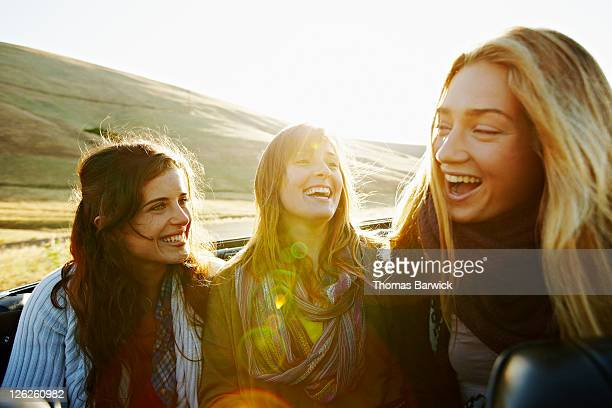Women sitting in convertible at sunrise laughing