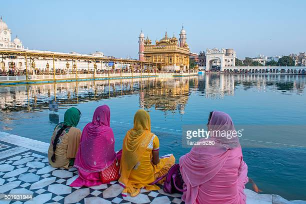 women sitting in front of golden temple, amritsar, india - amritsar stock pictures, royalty-free photos & images