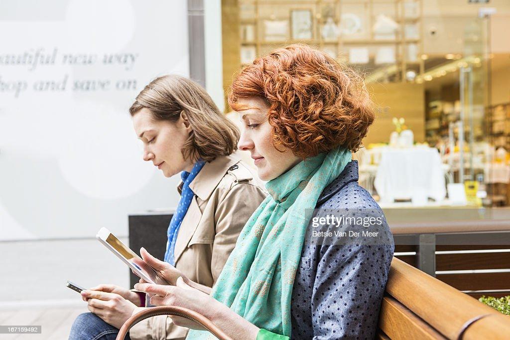 Women sitting in shopping area looking at internet : Bildbanksbilder