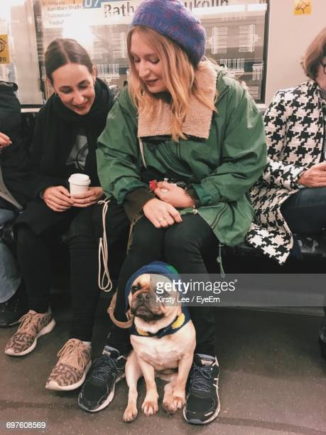 Women Sitting In Subway Train With Pug