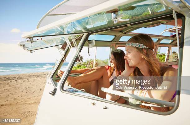 Women sitting in van on beach