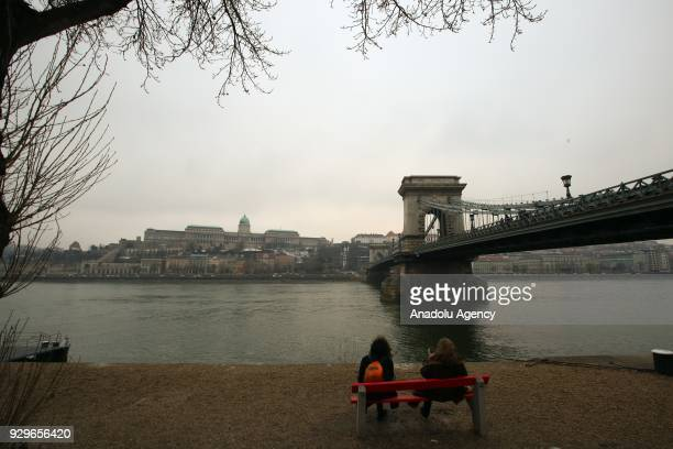 Women sitting on a bench near Danube river and Chain Bridge in Budapest Hungary on March 7 2018