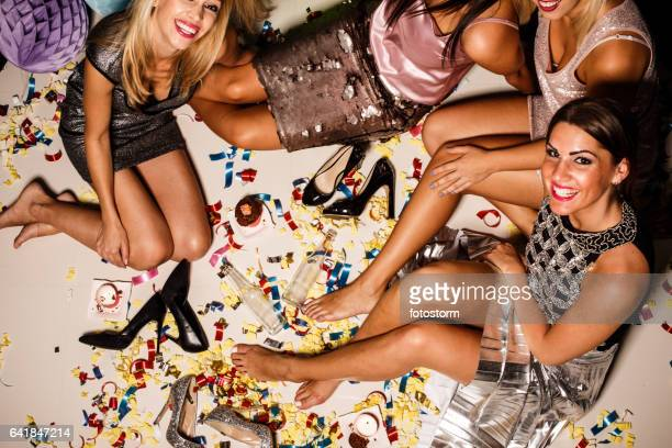 Women sitting on a messy floor after party