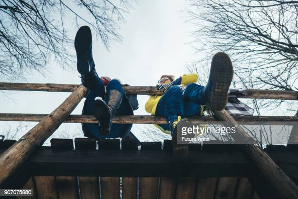 women sitting on a wooden fence - human leg stock pictures, royalty-free photos & images