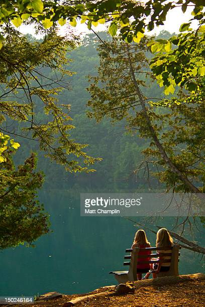 women sitting on bench at sunset - fayetteville stock pictures, royalty-free photos & images