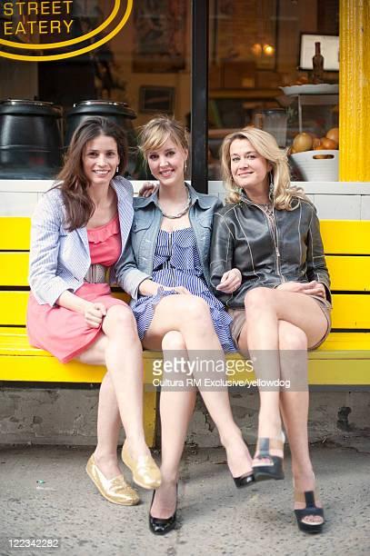 Women sitting on bench on city street