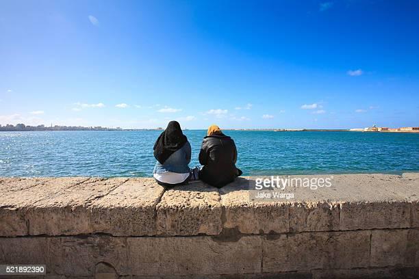 women sitting on city wall, alexandria, egypt - jake warga fotografías e imágenes de stock