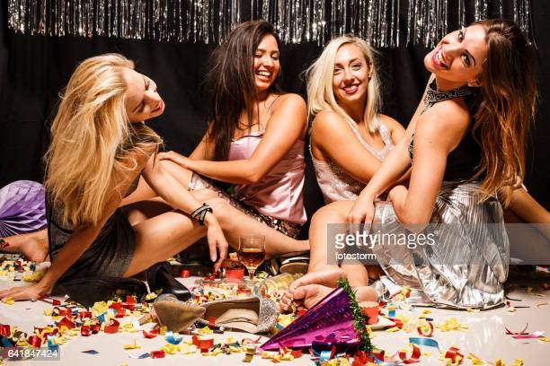 Women sitting on floor with confetti after party