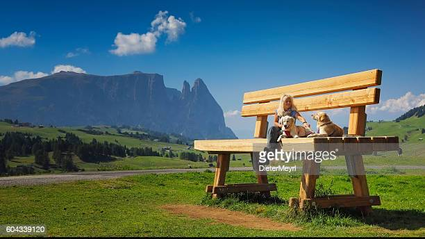 Women sitting on giant bank with her dogs, Seiser Alm