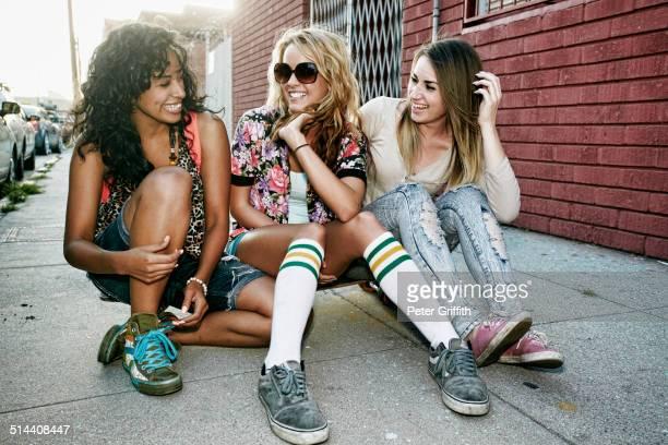 Women sitting on skateboard on city street