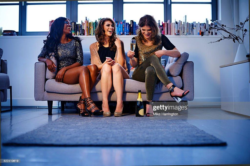 Women sitting on sofa enjoying drinks and laughing : Stock Photo
