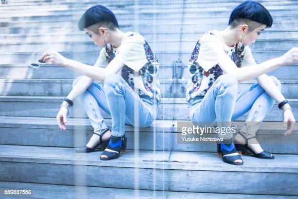 women sitting on the stairs - yusuke nishizawa stock-fotos und bilder