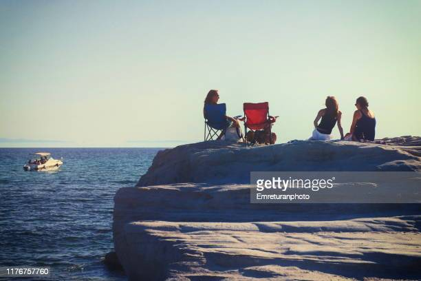 women sitting on top of a rock and an anchored boat near the coastline - emreturanphoto fotografías e imágenes de stock