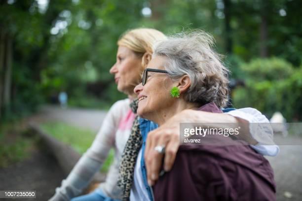 Frauen sitzen zusammen am Seeufer im Wald