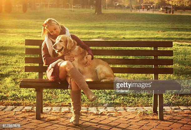 Women sitting with golden retriever in autumn park