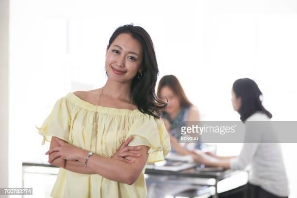 オフィスで微笑む女性 - 女子大生 ストックフォトと画像