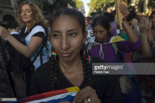 A women smiles during a mass demonstration as part of International Women's Day strike in demand for women's rights and gender equality on March 08...