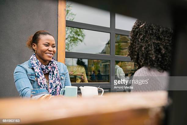 Women Smiling on cafe patio over Coffee
