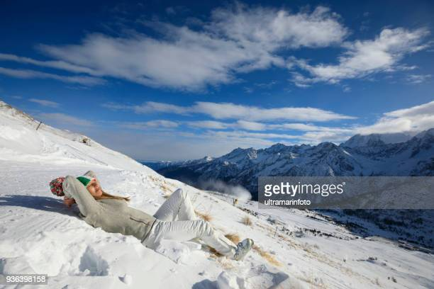 women, snow skier sunbathing, lying on the ground , enjoying on sunny ski resorts.  high mountain snowy landscape.  italian alps mountain of the dolomites  italy, europe. amateur winter sports. - winter sports event stock pictures, royalty-free photos & images
