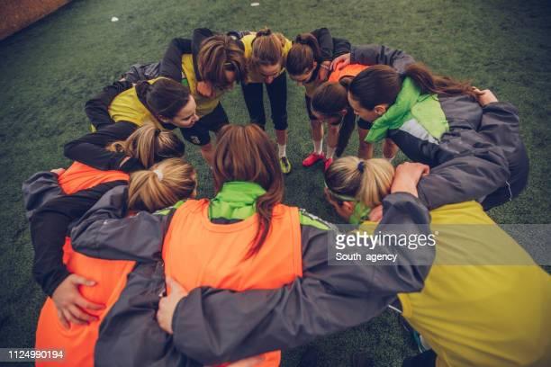 frauen fußball gruppe team hug - frauenfußball stock-fotos und bilder
