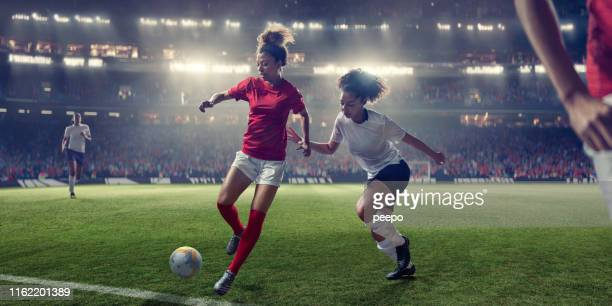 women soccer players in mid-action during game in floodlit stadium - kicking stock pictures, royalty-free photos & images