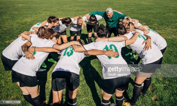 women soccer team and coach hugging - football team stock pictures, royalty-free photos & images