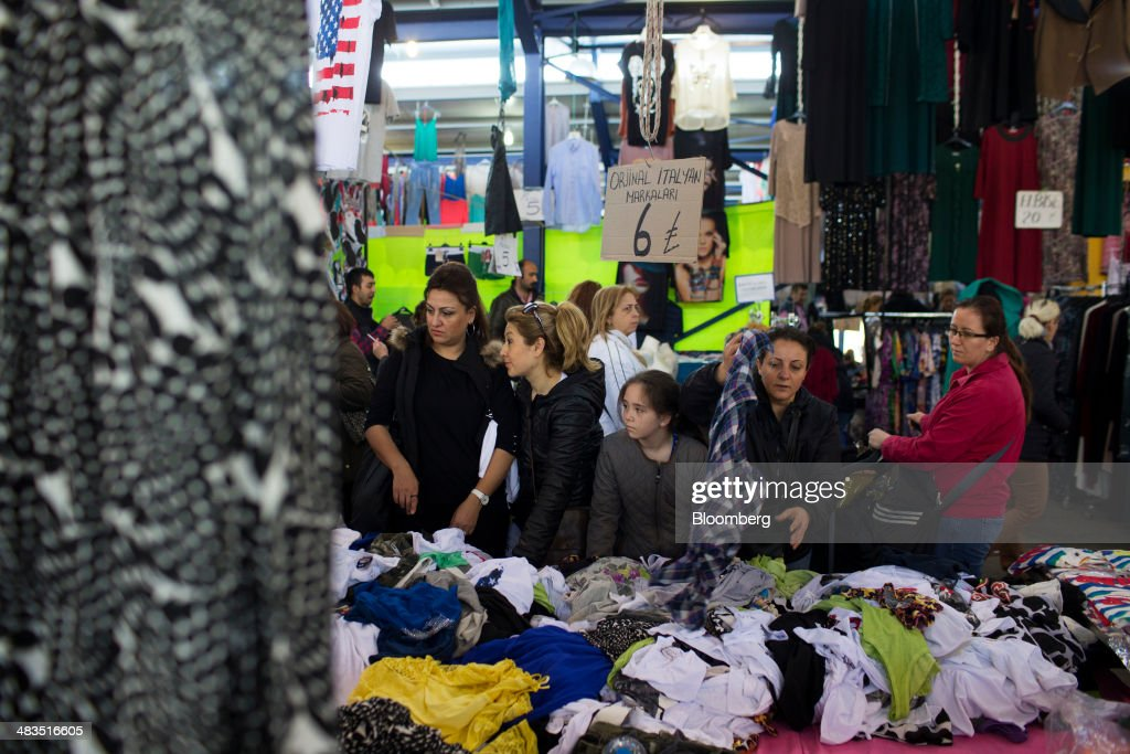 Women sort through clothes and materials for sale at a stall in the Yesilkoy street market in Istanbul, Turkey, on Wednesday, April 9, 2014. Turkish central bank Governor Erdem Basci indicated to analysts in London on April 3 that he planned to keep monetary policy tight to control inflation. Photographer: Kerim Okten/Bloomberg via Getty Images