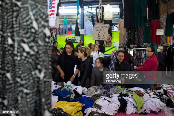Women sort through clothes and materials for sale at a stall in the Yesilkoy street market in Istanbul Turkey on Wednesday April 9 2014 Turkish...
