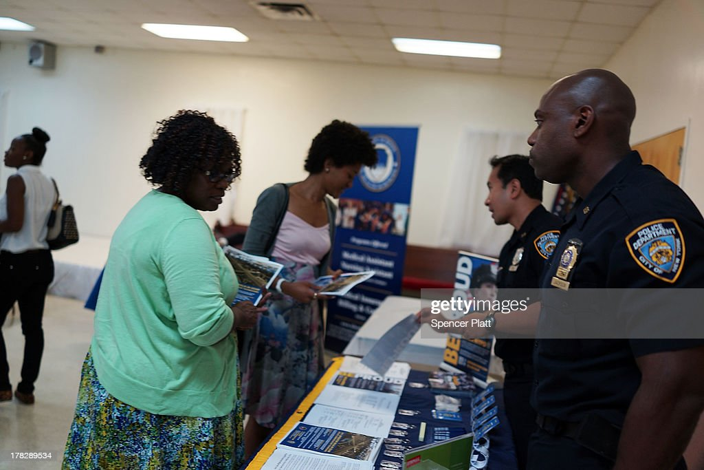 Women speak with an recruiters from the New York Police Department (NYPD) at the 'Beyond the Dream' job fair at the Brown Memorial Baptist Church in Clinton Hill, Brooklyn on August 28, 2013 in New York City. A new report by the Fiscal Policy Institute on New York's economy calls the last 10 years a 'lost decade' for typical workers. The report by the nonpartisan think tank found that median wages dropped almost 7 percent for men and about 1 percent for women.