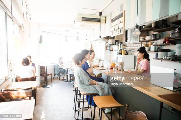 women spending their time in the afternoon cafe - サテン ストックフォトと画像